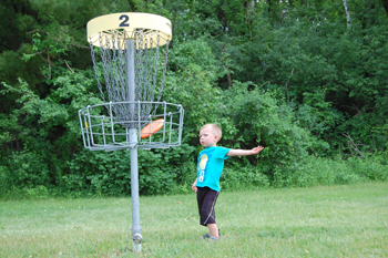 young boy playing disc golf