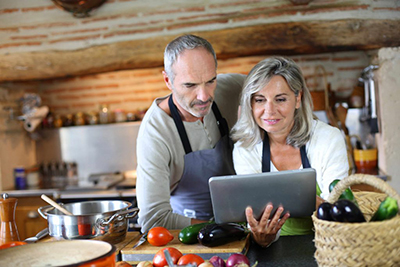 Couple in Kitchen Looking at Tablet