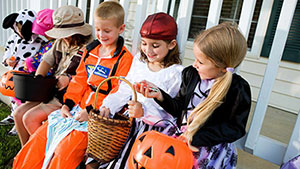a-group-of-children-in-Halloween-costumes-sitting-on-a-bench-looking-at-their-candy-and-treats