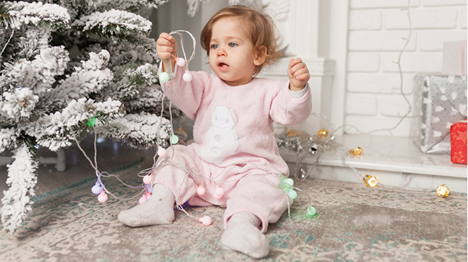 Baby playing with Christmas lights
