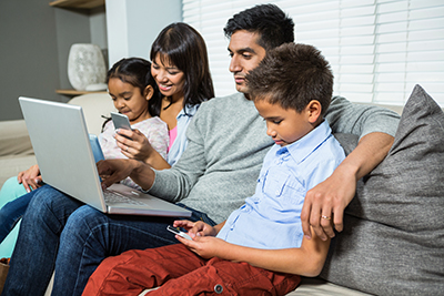 family-looking-at-screens-while-sitting-on-couch