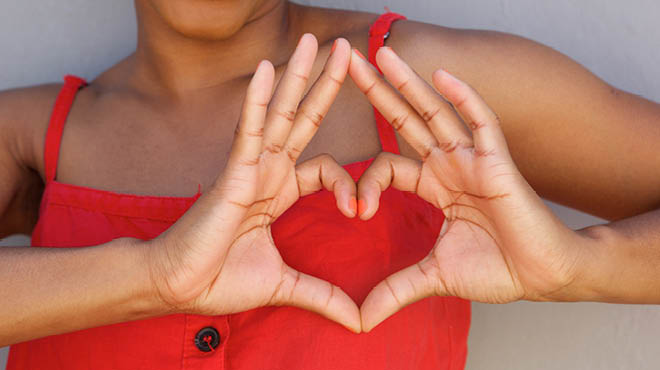 Hands making a heart shape over the chest