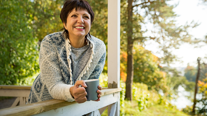 Happy woman leaning on deck with coffee