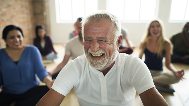 Mature man laughing during meditation class