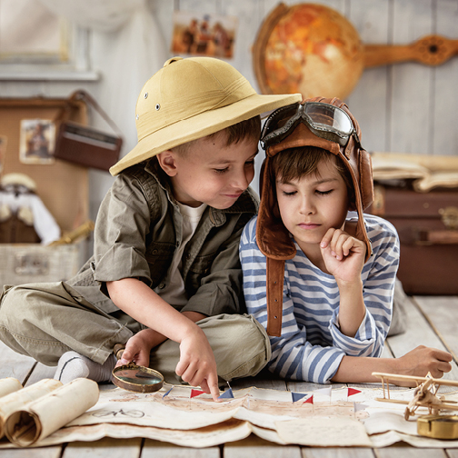 Two young boys exploring a map indoors