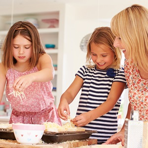 Two young girls and mother preparing a meal