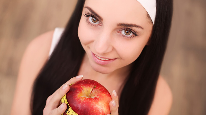 Young woman holding an apple with measuring tape