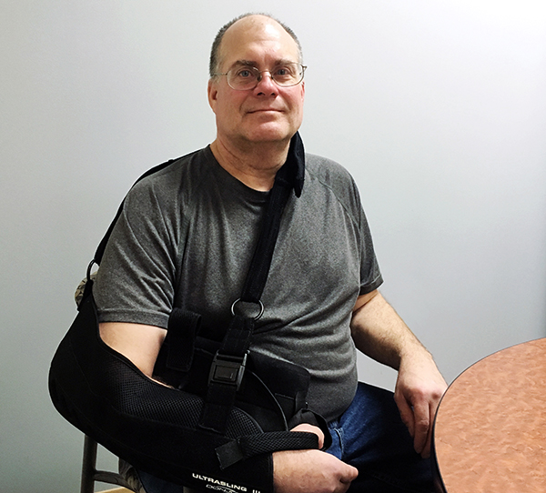 patient-dan-boswell-sitting-at-table-with-arm-in-sling