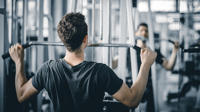 Man using a lat bar in gym