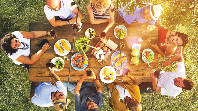 People sitting around a picnic table of food