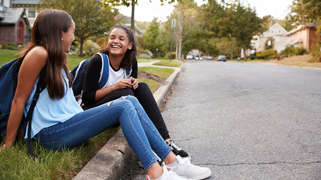 Teen girls sitting on curb smiling
