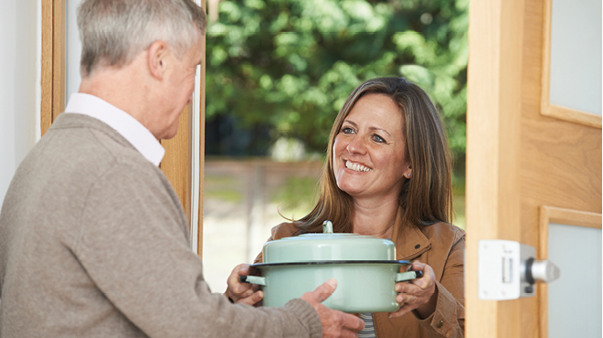 Woman delivering food to older man