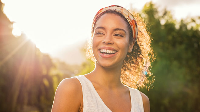 Young woman smiling with sun shining in the background