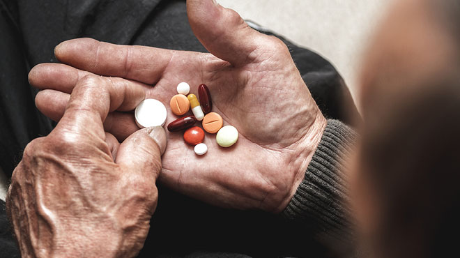 Elderly palm of hand holding medications