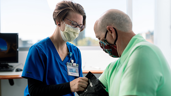 Nurse in blue scrubs wearing mask treats patient in green shirt wearing mask