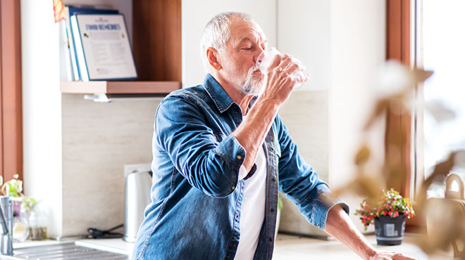 Older man drinking glass of water