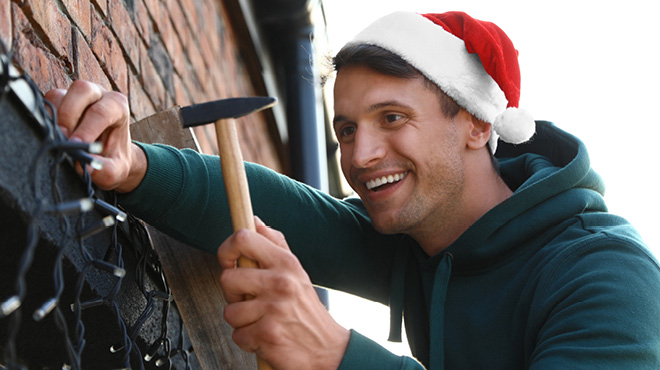 Man with Santa hat putting up holiday or Christmas lights on house