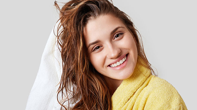 Smiling woman towel drying hair