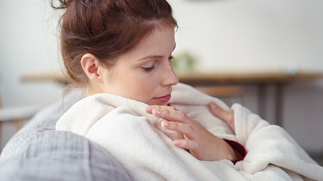 Woman hugging self in blanket
