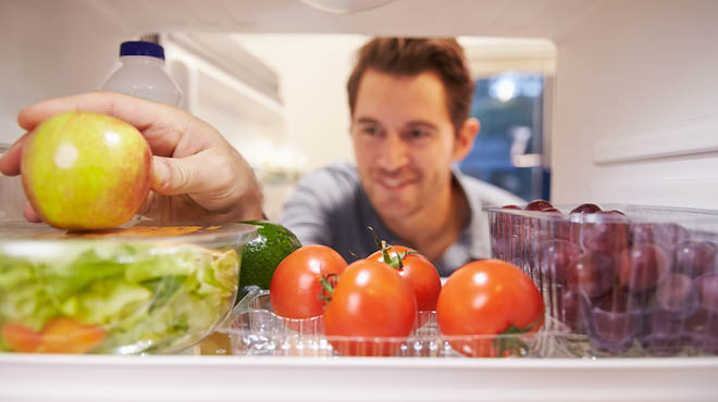 Looking inside refrigerator with fruits and lettuce