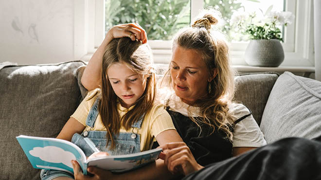 Mom and daughter reading book on sofa