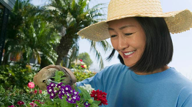 Smiling person with hat flower gardening