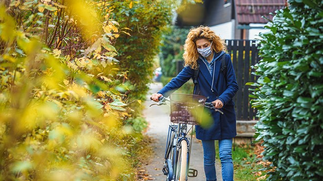 Walking bicycle on the sidewalk in fall