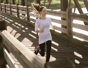 Woman running on foot bridge
